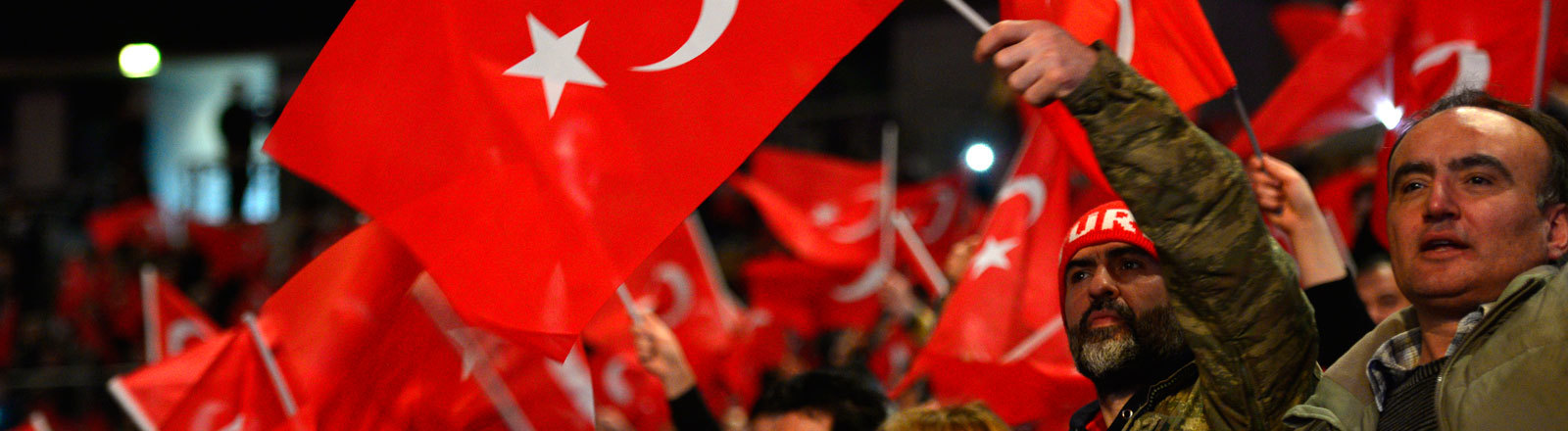 This file photo taken on February 18, 2017 shows participants waving Turkish flags during an event with the Turkish Prime Minister to promote a constitutional referendum in Oberhausen, western Germany. Turkish politicians will hold no further rallies in Germany ahead of April's referendum on expanding President Recep Tayyip Erdogan's powers, his AKP party said on March 20, 2017 amid a heated diplomatic row.