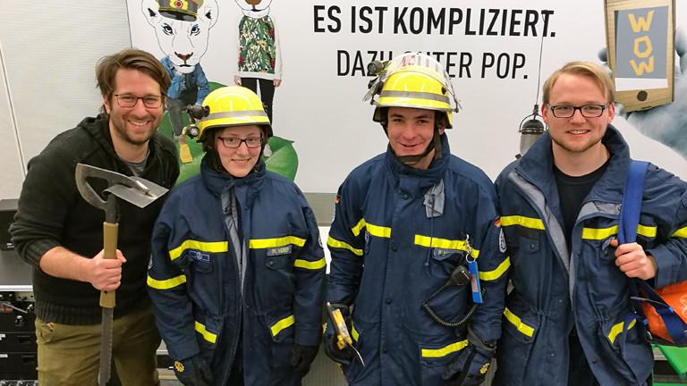 Sebastian Sonntag mit drei Studierenden der FH Koblenz in THW-Montur.