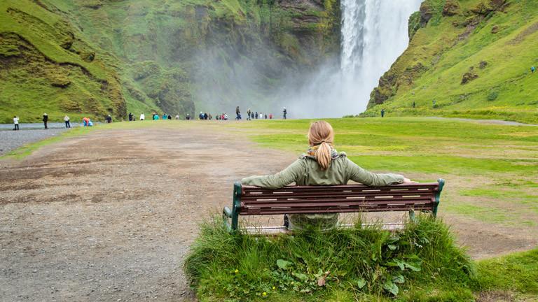 Katharina Finke sitzt auf einer Bank vor einem Wasserfall auf Island