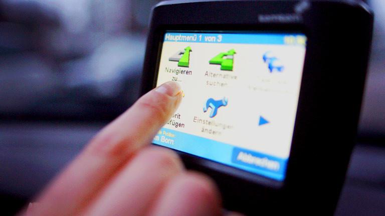 Ein Autofahrer bedient ein Navigationsgerät