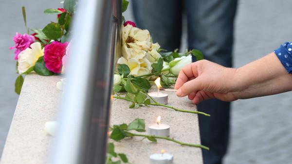 Eine Frau entzündet Kerzen am 23.07.2016 am Zugang zur U-Bahnstation Olympia-Einkaufszentrum in München (Bayern), den die Polizei nach einer Schießerei mit Toten und Verletzten am Vortag abgesperrt hat. Die tödlichen Schüsse hat ein 18-jähriger Deutsch-Iraner abgegeben. Zehn Menschen starben.