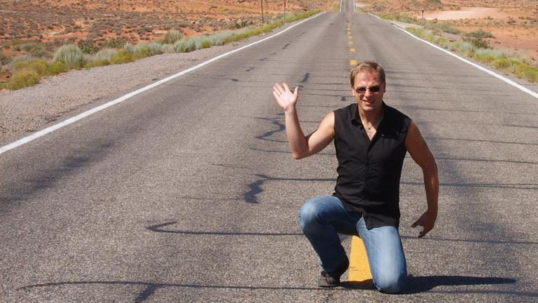 Peter Schmidt kniet auf einer Straße