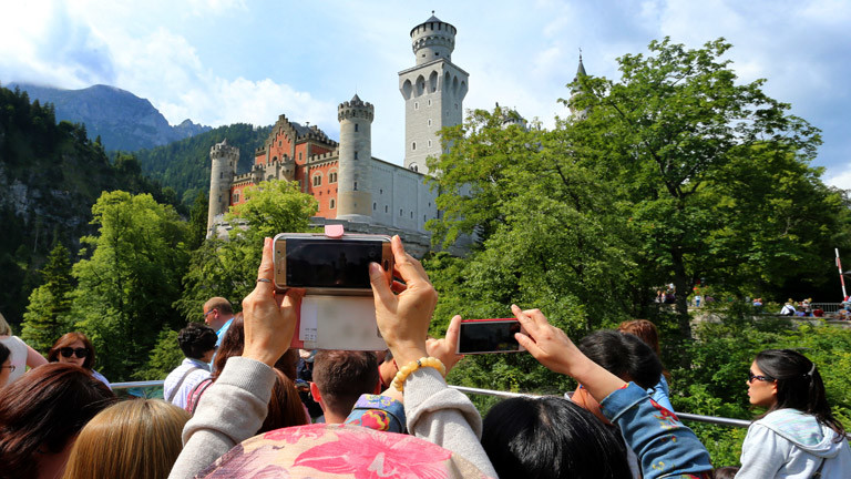 Ein Tourist fotografiert mit einem Handy das Schloss Neuschwanstein