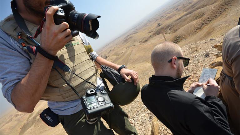 Fotograf mit Kamera und Journalist in der Wüste.
