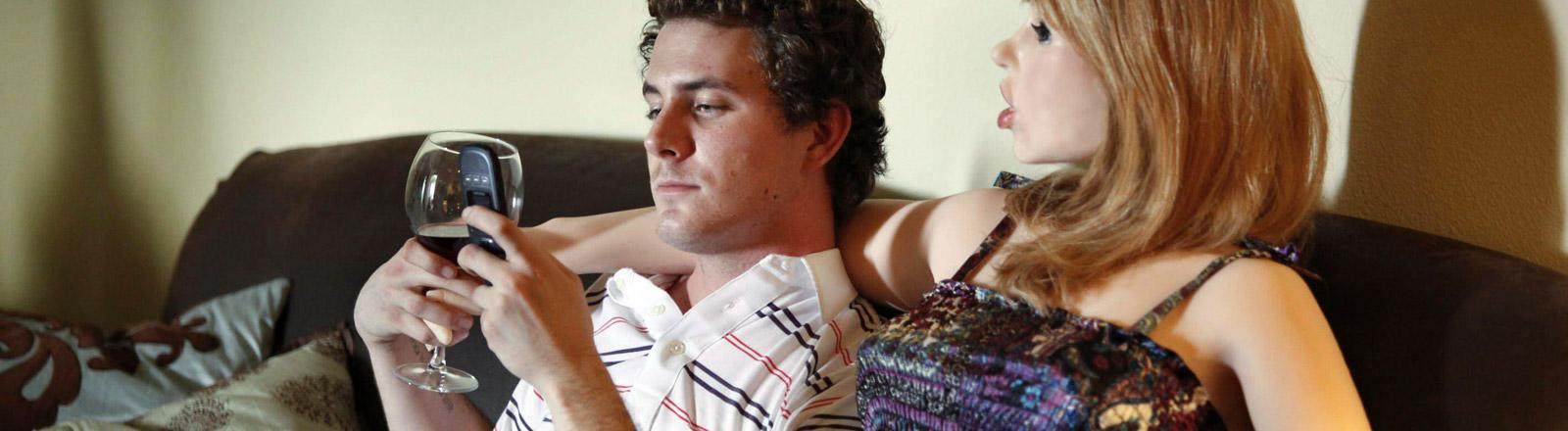 Ein Mann sitzt mit einem Sexroboter auf einer Couch