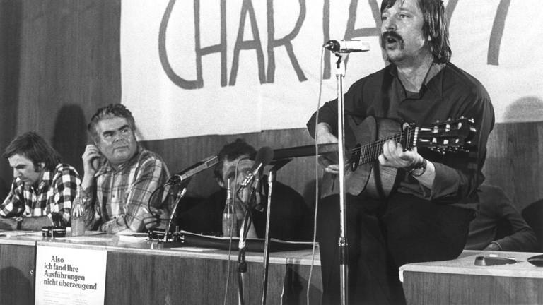 Der aus der DDR ausgebürgerte Liedermacher Wolf Biermann (r.) tritt am 27.03.77 im Saal des Frankfurter Gewerkschaftshauses in einer Solidaritätsveranstaltung für die Bürgerrechtsbewegung in der CSSR