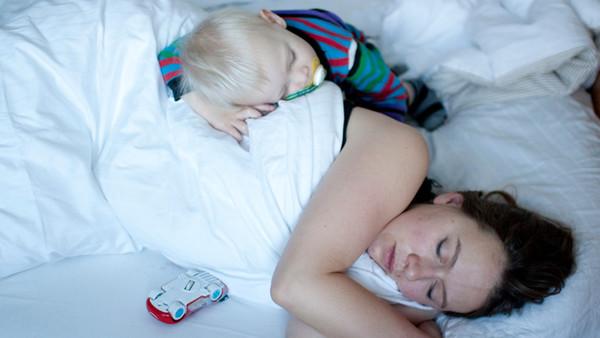 Schlafende Mutter mit Kind im Bett