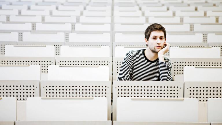 Ein junger Mann in einem Hörsaal.
