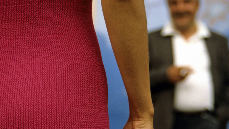 Eine Frau im roten Strickkleid wird von einem älteren Mann beobachtet.