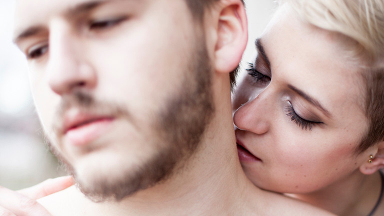 Frau schnuppert am Nacken eines Mannes