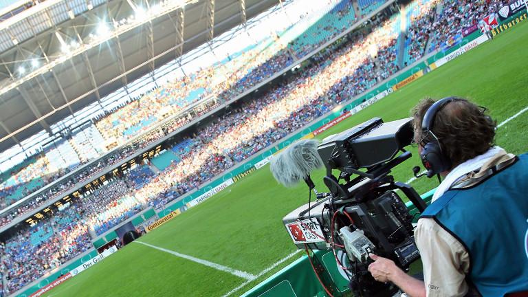 Ein Kameramann filmt ein leeres Fußballfeld in einem vollen Stadion.