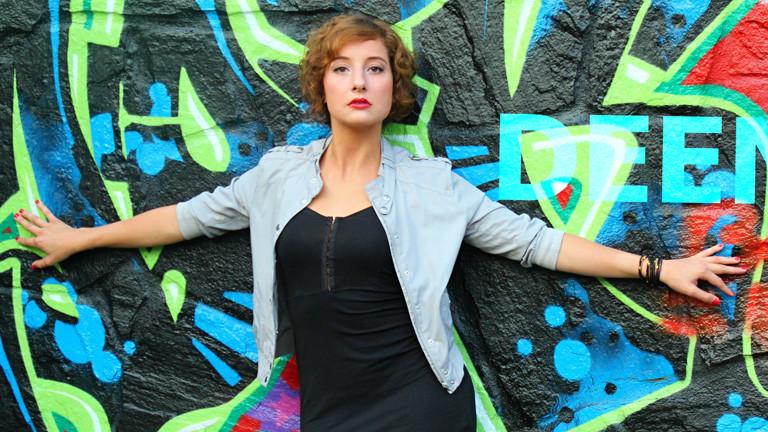 Die Sängerin Deena steht vor einer Wand mit Graffiti. Sie trägt ein schwarzes Kleid, mit Jacke darüber. Sie hat kurze, braune Haare.