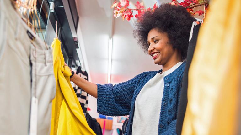 Hindi Kiflai durchsucht in Frankfurt am Main in einem Geschäft für Secondhand-Mode einen Kleiderständer.