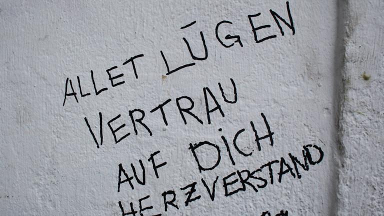 """Die Worte """"Allet Lügen vertrau auf Dich Herzverstand"""" sind am 11.12.2017 in Berlin mit Filzstift auf eine Hauswand geschrieben."""