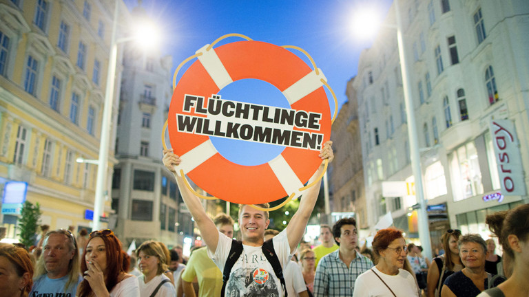 """Demonstranten halten in Wien ein Schild mit der Aufschrift """"Flüchtlinge willkommen"""" in die Höhe"""