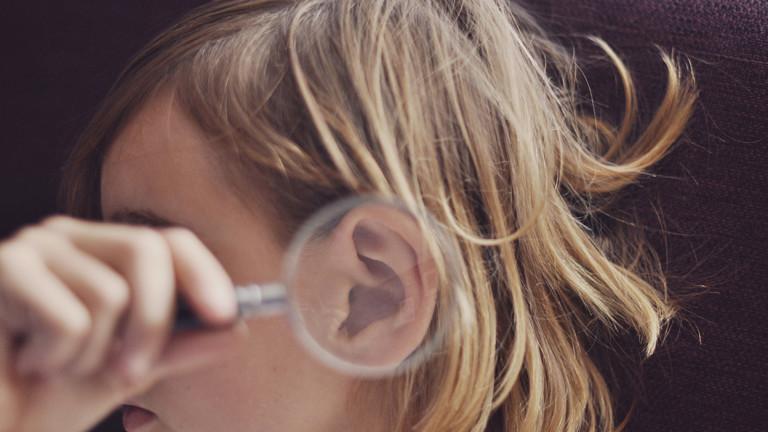 Eine Frau hält sich eine Lupe ans Ohr
