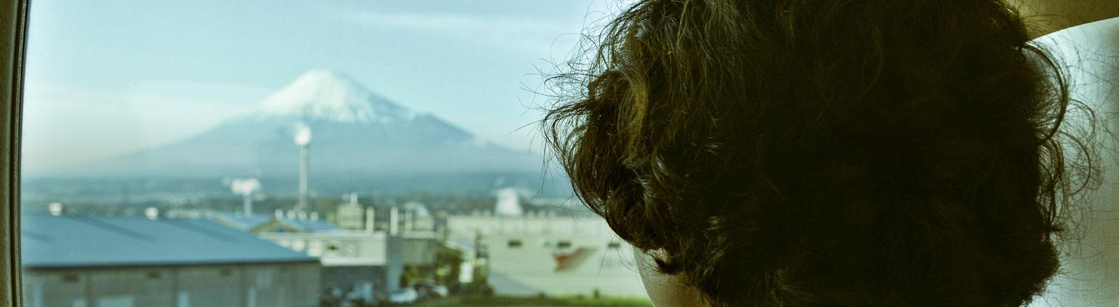 Eine Frau blickt aus einem Flugzeugfenster auf den Fuji-Berg in Japan.