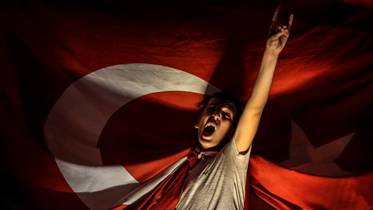Ein junge jubelt frenetisch unter der türkischen Nationalflagge.