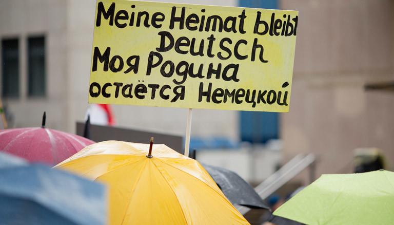Regenschirme und ein Plakat auf einer Demonstration von Russlanddeutschen.