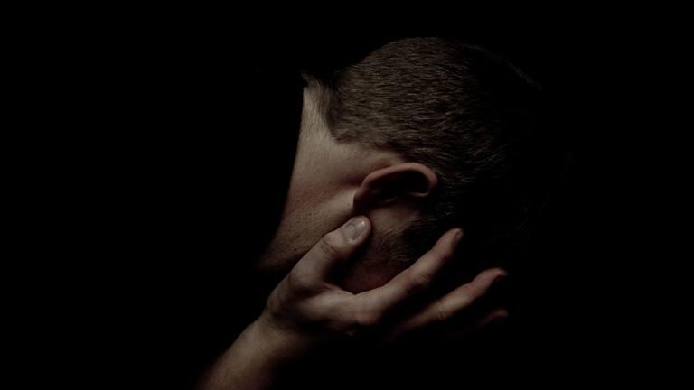 Ein Mann hält seinen Kopf in den Händen.