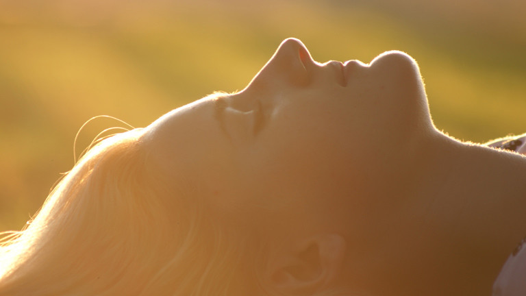 Frau liegt träumend auf dem Rücken.