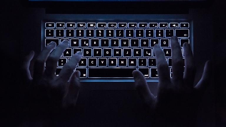 Mann schreibt auf beleuchteter Tastatur.