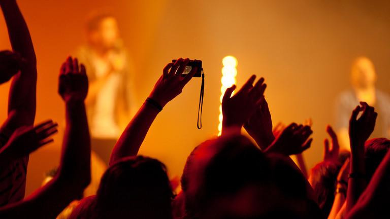 Publikum bei einem Konzert reckt die Arme in die Höhe