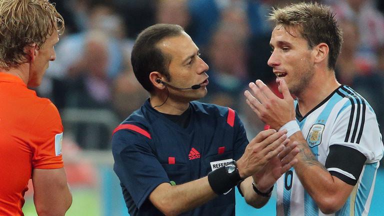 Der türkische Schiedsrichter Cüneyt Cakir spricht mit dem argentinischen Spieler Lucas Biglia.