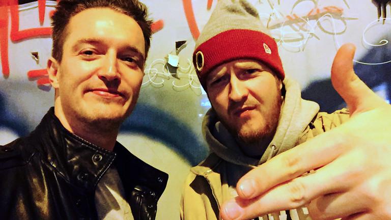 Zwei Männer vor einem Graffiti
