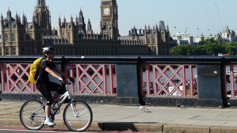 Eine Radfahrerin fährt über eine Brücke, im Hintergrund der Big Ben und Westminster.