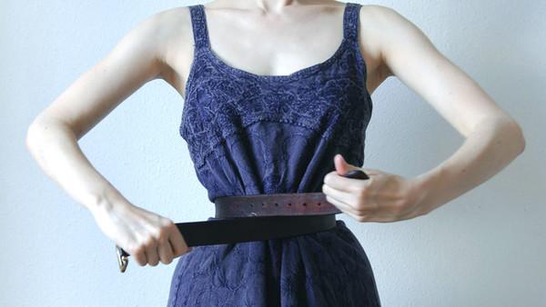 Eine Frau umschnürt ihre Taille mit einem Gürtel.