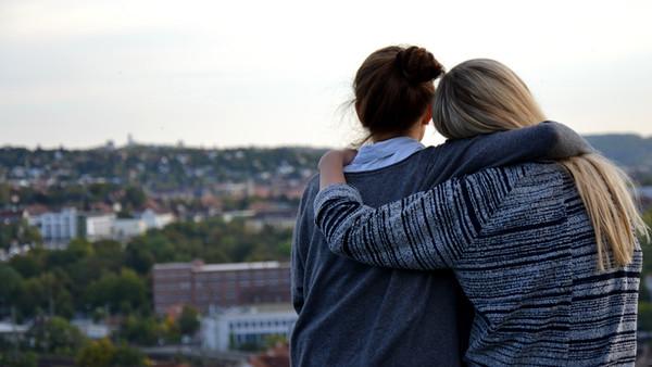 Jugendliche umarmen sich. Sie blicken sehnsuchtsvoll auf eine Stadt. Sie haben eine Freundschaft.