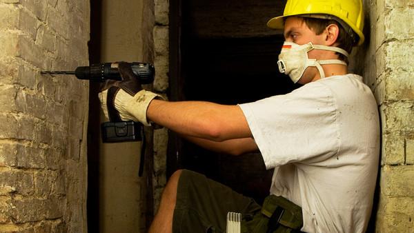 Ein Mann bohrt mit einem Akkuschrauber in eine Mauer.