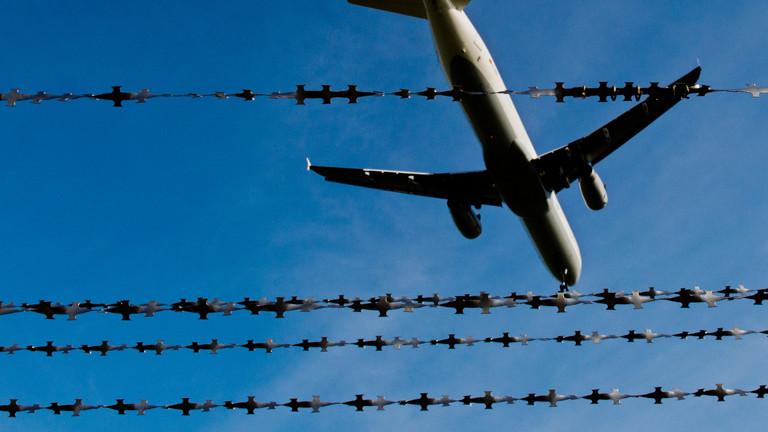 Flugzeugstart am Himmel hinter dem Zaun. dpa
