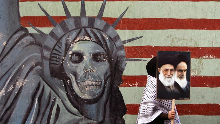 Eine iranische Studentin hält ein Poster Ajatollah Chamenei und dem früheren Ajatollah Chomenei während sie vor einer Wandmalerei an der ehemaligen US-Botschaft vorbei geht. 30. Jahrestag der Erstürmung der US-Botschaft.