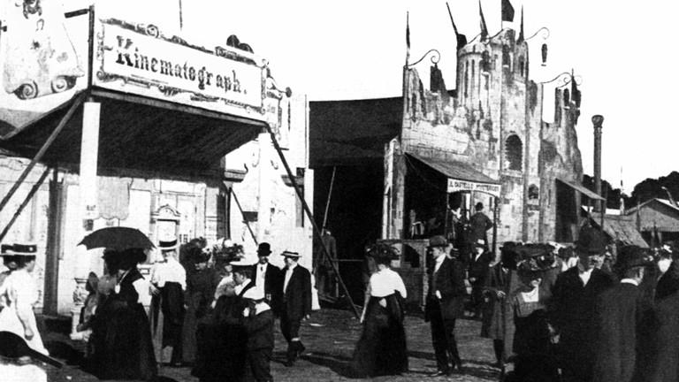 Auf einem Volksfest auf der Festwiese in Berlin-Schönholz im Jahr 1910 steht ein Kinematograph - ein Vorläufer des Kinos.