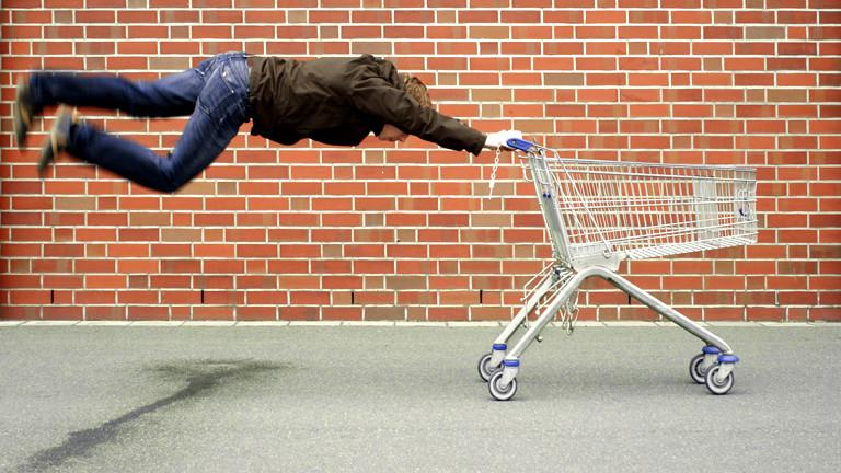 Ein Mann fliegt hinter seinem Einkaufswagen her.