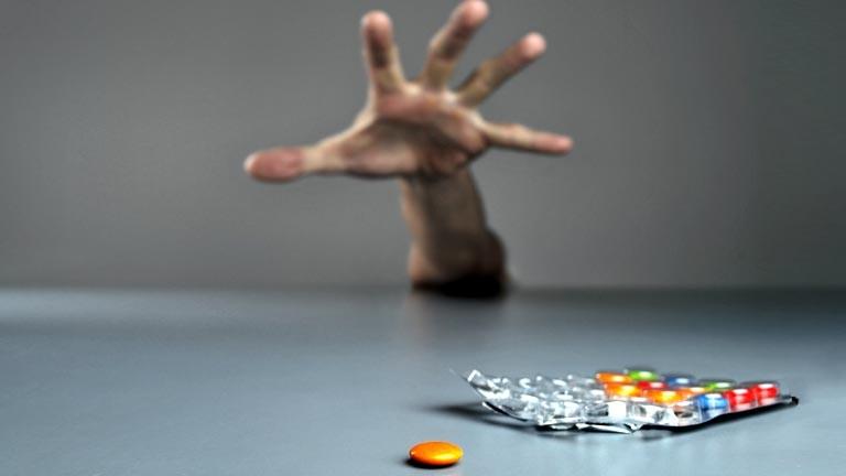 Ein Mann greift nach einer Tablettenpackung