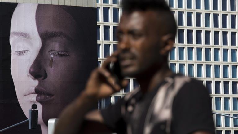 Ein Afro-Amerikaner geht bei einer Demo gegen Rassismus eine Straße lang.