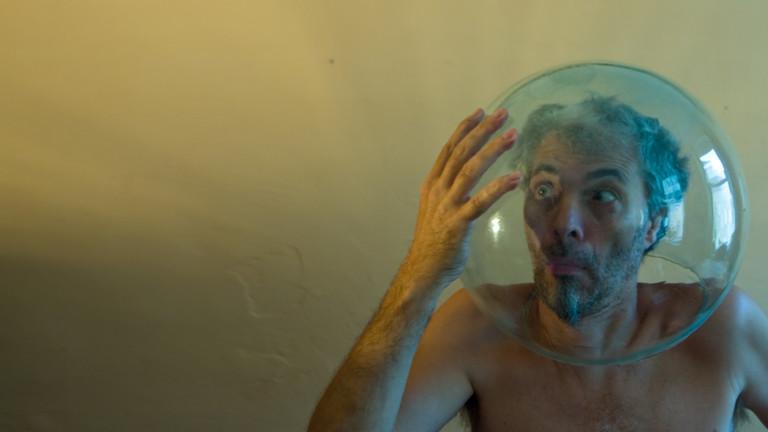 Ein Mann sitzt bei sich zu Hause am Tisch und hat eine Glaskugel auf dem Kopf. Sieht aus wie ein Taucher oder Astronaut.
