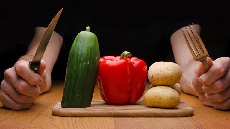 Ein Mann sitzt mit einem Messer und einer Gabel hinter einem Brett mit Gemüse.