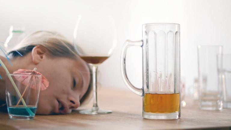 Eine Frau, die einen Kater hat, nach dem sie zu viel Alkohol getrunken hat.