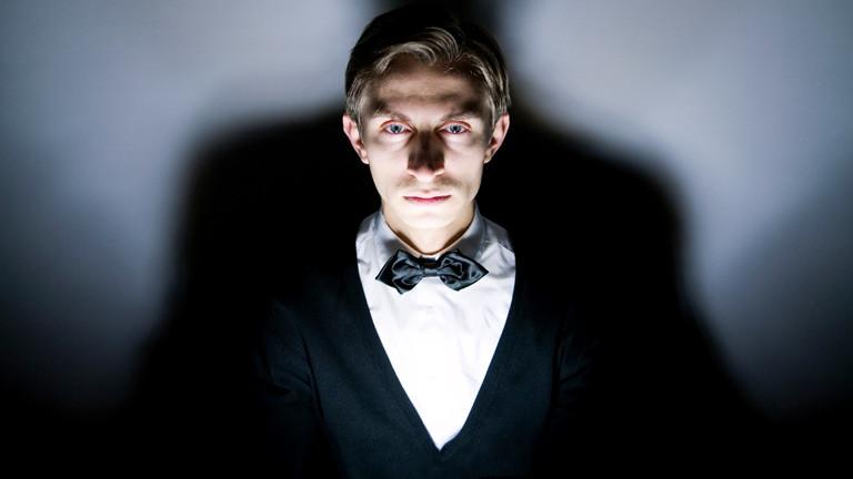 Ein bedrohlich wirkender junger Mann mit einer Fliege und einem weißen Hemd.