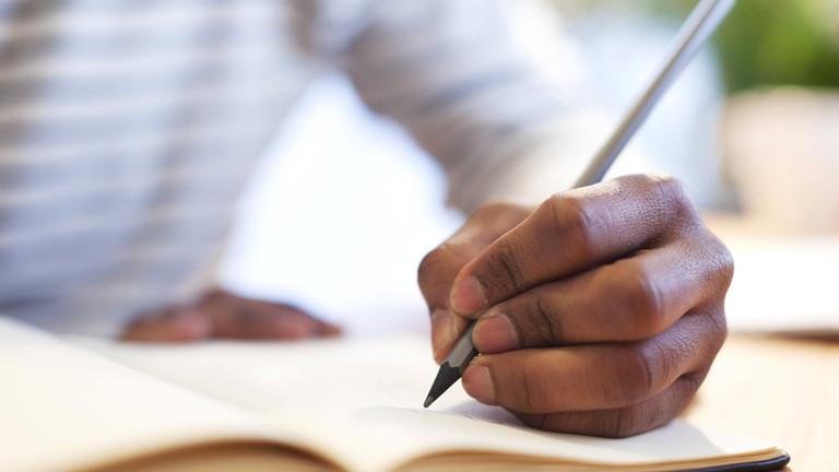 Linkshänder schreibt in ein Buch