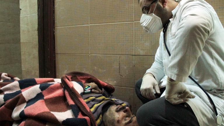 Ein syrischer Arzt mit einem Verletzten in Aleppo.