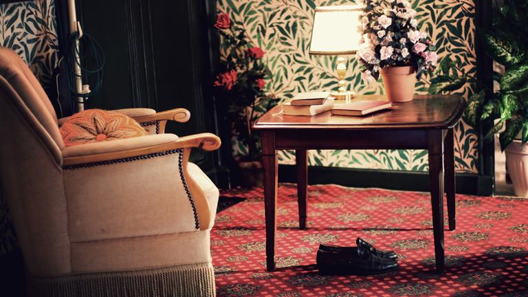 Antiquiertes Wohnzimmerszenario mit Sessel, Teppich und Tisch.
