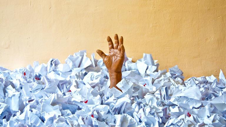 Eine Hand ragt aus einem Haufen Papier