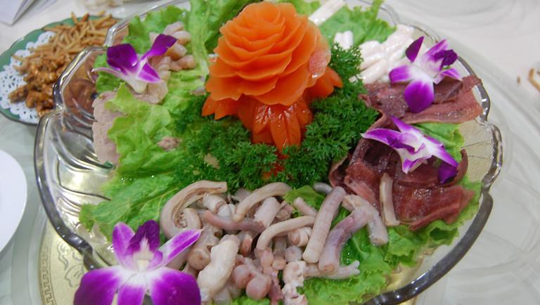 Schildkröten-Hirschpenistopf angerichtet mit asiatischer Blüten und Gemüsedekoration