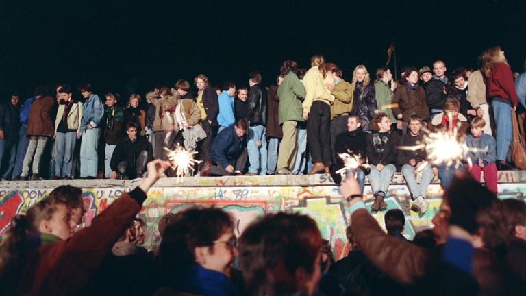 Einen Tag nach der Grenzöffnung in Berlin feiern tausende Menschen auf, vor und hinter der Berliner Mauer am Brandenburger Tor