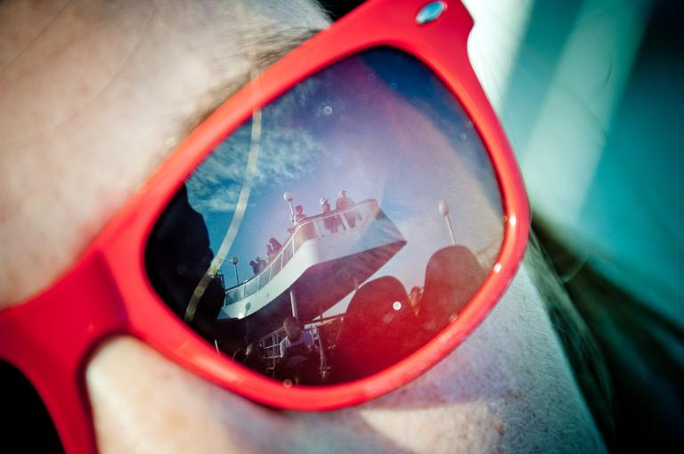 Eine Frau trägt eine rote Sonnenbrille, nur ihr Gesicht ist zu sehen. In der Brille spiegelt sich das Deck eines Schiffes.
